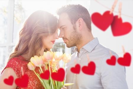Romantic couple embracing each other with red hanging hearts
