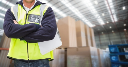 Mid section of worker standing with arms crossed in warehouse Stock Photo