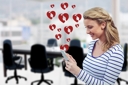 Composite image of woman using mobile phone with digitally generated red heart Stock Photo