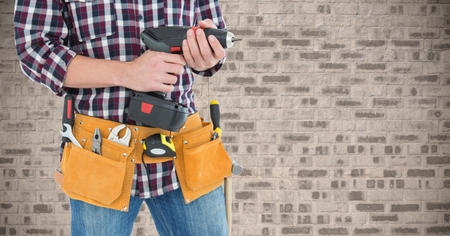 tool belt: Mid section of handyman with tool belt and drill machine against brick wall Stock Photo