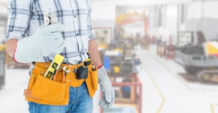 Mid section of handyman with tool belt at workshop