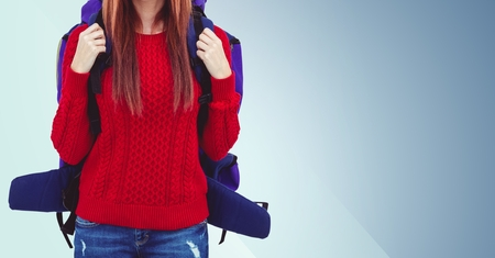 mladistvý: Mid section of woman with backpack against blue background