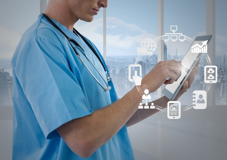 Mid section of male nurse using digital tablet with app icon interface screen