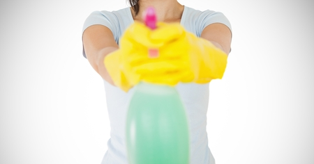 odcisk kciuka: Mid section of female cleaner with yellow gloves holding a bottle Zdjęcie Seryjne