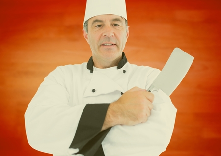 Portrait od male chef holding chopping knife against orange background