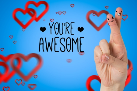 Smiling couple fingers with digitally generated hearts and message against blue background