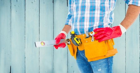 tool belt: Mid section of handyman with tool belt and sprit level against wooden background Stock Photo