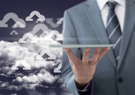 smother: Digital composite image of businessman holding digital tablet against sky background