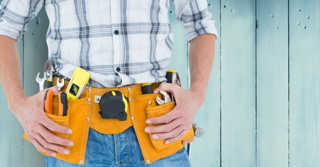 tool belt: Mid-section of handy man with tool belt against blue wood panel Stock Photo