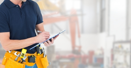 tool belt: Mid section of construction man with tool belt writing on clipboard