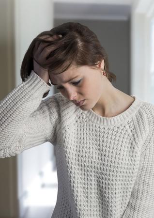 dreariness: Digital composite of Sad depressed woman holding head against hall