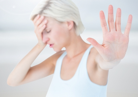 dreariness: Digital composite of Sad stressed woman holding out hand against bright background Stock Photo