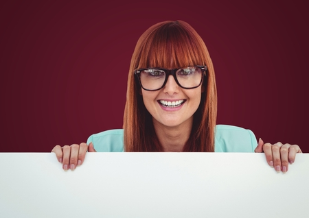 Digital composite of Woman in glasses with large blank card against maroon background