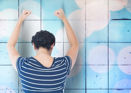 uneasy: Digital composite of Sad angry woman grief banging fists against a blue wall