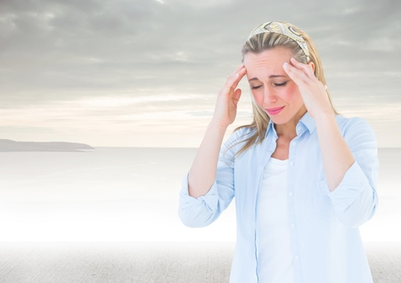 Digital composite of Stressed woman headache in front of sea