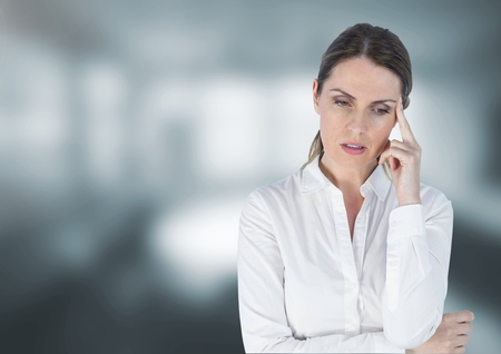 pounding head: Digital composite of Sad disappointed businesswoman against blurred grey background