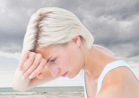 dreariness: Digital composite of Sad tired woman against cloudy sky and ocean