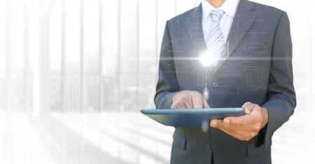 man holding transparent: Digital composite of Business man mid section with tablet and white interface with flare against blurry window