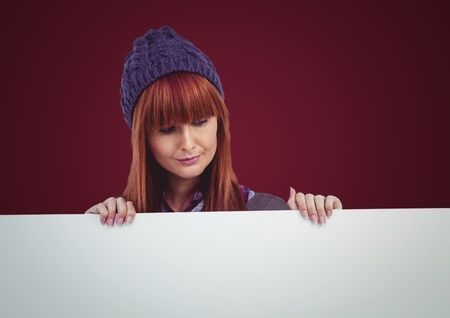 Digital composite of Woman in hat with large blank card against maroon background Stock Photo