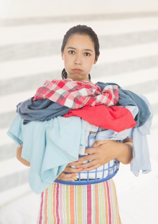 Digital composite of Tired upset woman with laundry basket against bright background Stock Photo