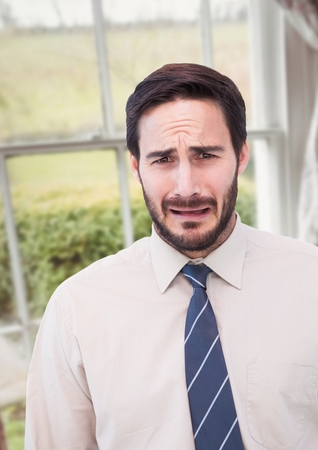 Digital composite of Businessman worried crying against countryside window