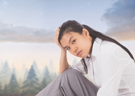 Digital composite of Tired disappointed young woman against magical sky Stock Photo