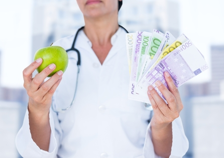 Digital composite of Doctor mid section with apple and money against blurry buildings