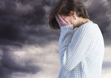 dreariness: Digital composite of Sad woman with face in hands against dark clouds Stock Photo