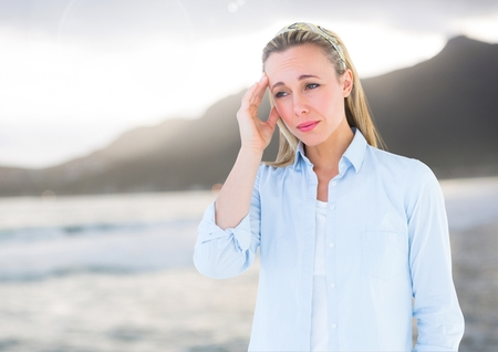 pounding head: Digital composite of Stressed headache woman by sea and mountains