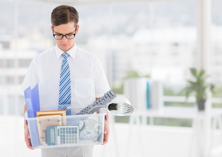 Digital composite of Businessman redundant with belongings in box in office