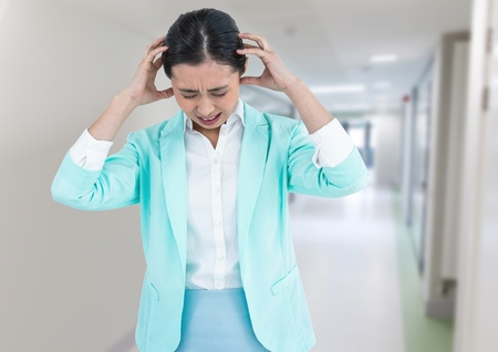 Digital composite of Stressed woman in corridor Stock Photo