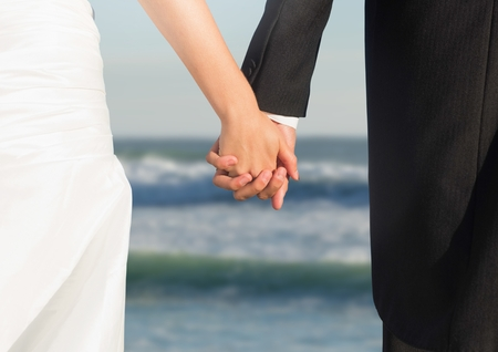 Digital composite of Wedding couple holding hands by sea