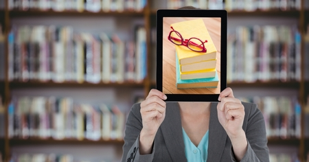Digital composite of Business woman with tablet over her face with piles of books while standing at  library