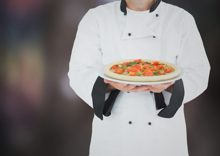 whites: Digital composite of Chef with pizza against blurry dark grey background Stock Photo