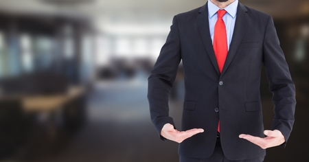 Digital composite of Business man mid section with palms up in blurry room Stock Photo