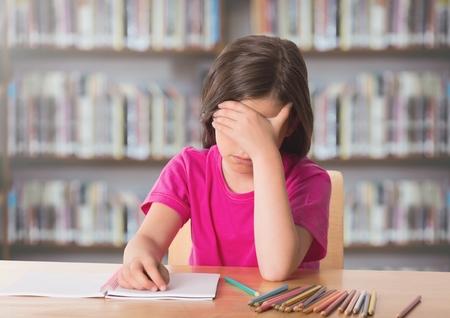 Digital composite of Sad girl at desk against bookshelves Stock Photo