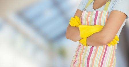 cleaning service: Digital composite of Woman in apron with arms folded against blurry window