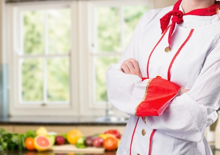 Digital composite of Chef arms folded against blurry kitchen with vegetables
