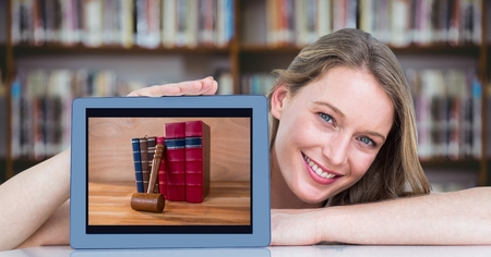 Digital composite of Happy woman presenting tablet with pile of books while sitting at desk in library Stock Photo