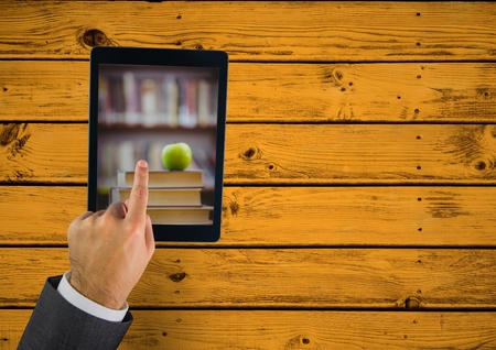 man holding transparent: Digital composite of Hand touching tablet showing book pile with apple on yellow table