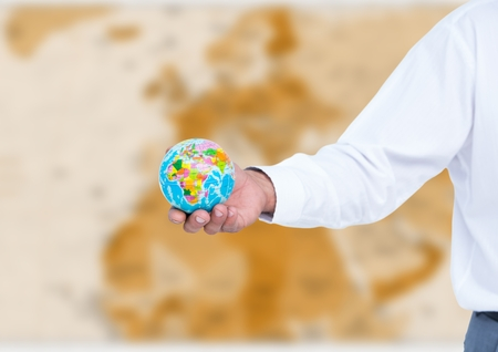 Digital composite of Arm with globe against blurry brown map Stock Photo