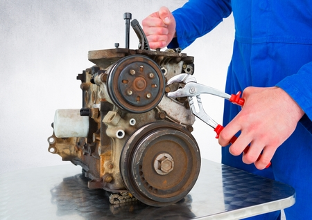 Digital composite of Mechanic working on machine against white wall
