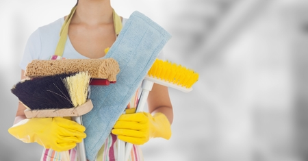 Digital composite of Woman in apron with brushes against blurry grey room