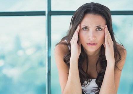 pounding head: Digital composite of Stressed worried woman against window