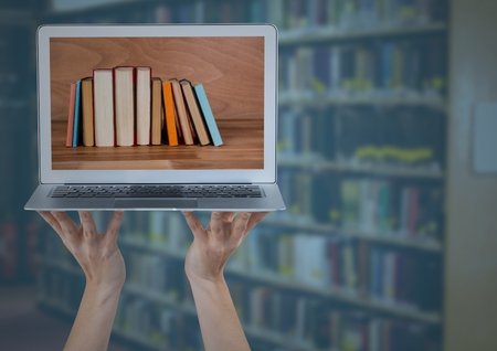Digital composite of Hands with laptop showing book spines against blurry bookshelf with blue overlay