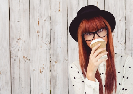 白い木製パネルに対して顔の上のコーヒー カップの水玉シャツの女性のデジタル合成