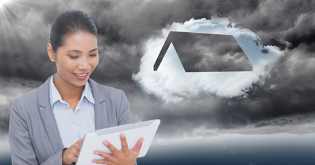 classy house: Digital composite of Business woman behind flare with tablet and cloud with roof against stormy sky Stock Photo