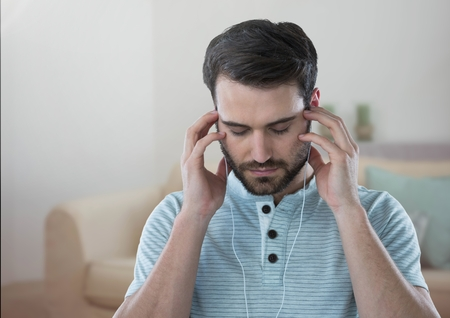 Digital composite of Stressed man on headphones relaxing at home Stock Photo