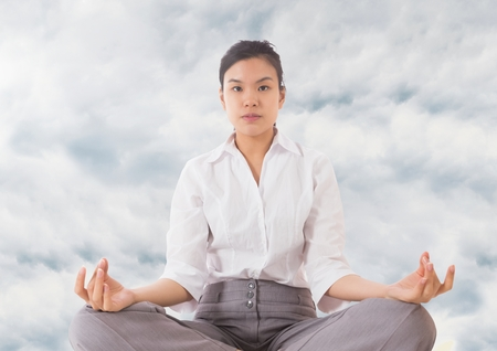 Digital composite of Woman Meditating by clouds