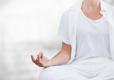 Digital composite of Womans hand Meditating with bright background Stock Photo